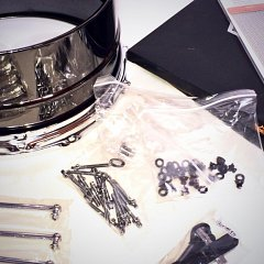 A table full of parts for a snare drum repair